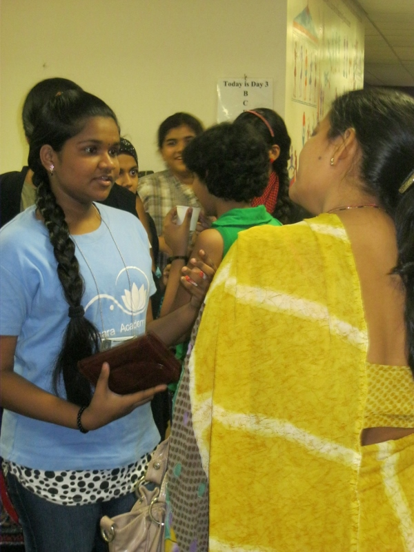 Current Avasara Leadership Fellow Divya P reassures a mother about the teaching quality