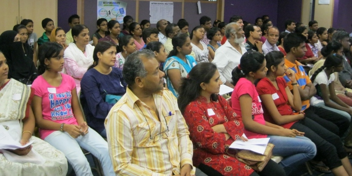 Parents and girls listen as Mangala welcomes the new Fellows