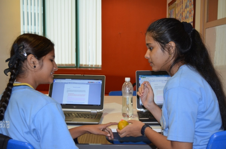 Sweety and Rosbin discuss their observations and hypothesis before adding to their Google Doc.