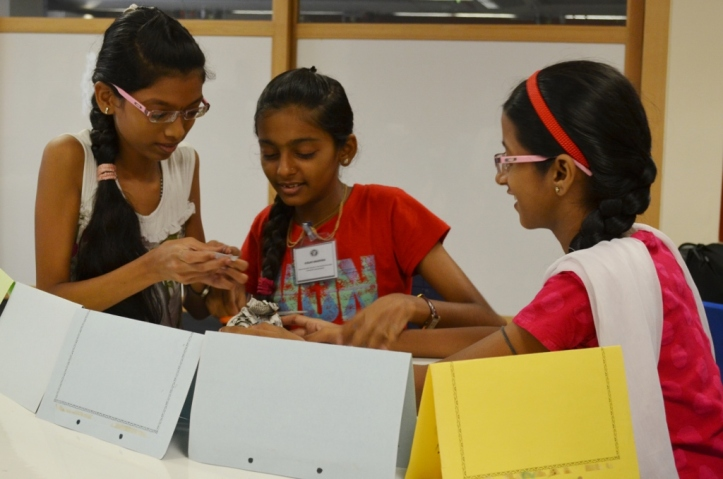 Nivedha, Gunjan and Afsana work on a project on their first day...keeping it secret by hiding it behind their name placards!